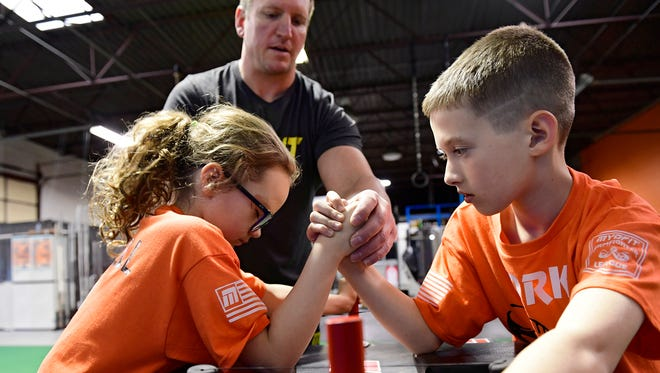 The Cornell siblings arm wrestle with the help of Coach Chad Eckert at a York Armfighters practice on April 10, 2018. The Armfighters are a youth arm wrestling club team that is a member of the Myofit Junior Armfighter league. The team is hoping to compete in a junior nationals event in Orlando in November.