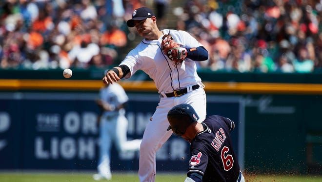 Tigers shortstop Jose Iglesias (1) makes a throw to first to complete a double play as Indians right fielder Brandon Guyer (6) slides into second in the fourth inning of the Tigers' 6-0 loss to the Indians on Wednesday, May 16, 2018, at Comerica Park.