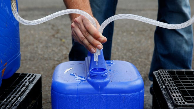 A Salem Public Works employee fills up a container with water at a water distribution site in Bush's Pasture Park in Salem, Oregon, on Friday, June 8, 2018.