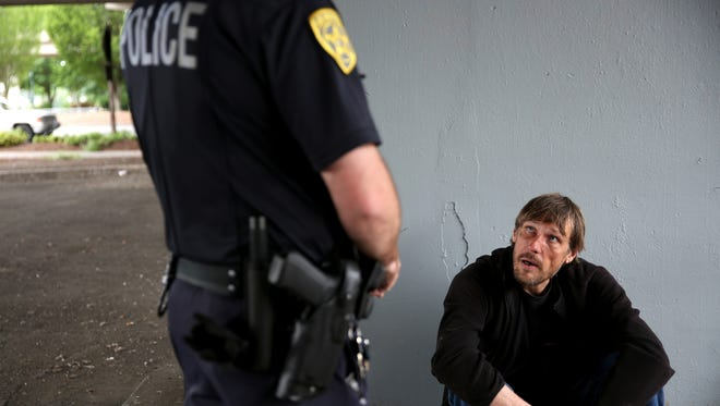 Salem Police Officer Andrew McFerron talks with Jonathan Jones, 49, who has been homeless in Salem for more than a year under the Center Street bridge in downtown Salem on Friday, May 25, 2018. Officer McFerron gave Jones a warning for trespassing after checking in with his patrol officer.