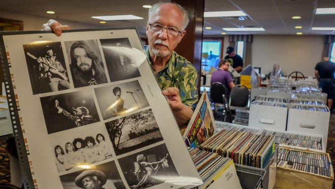 Vendor Greg Wilcox, displays one of over 300 vintage rock posters he has from the Fillmore Auditorium at the Lansing Record & CD Show Saturday, July 7, 2018.