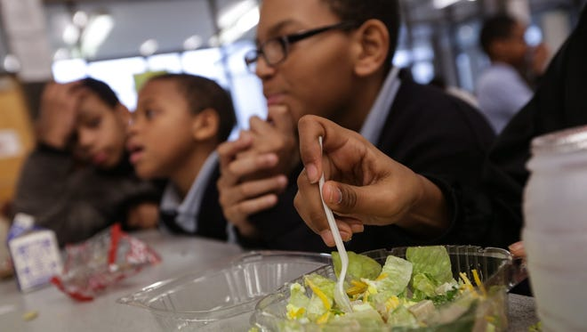 Bates Academy student Destiny Taylor works on eating her salad during lunch on Dec. 16, at the school in Detroit.