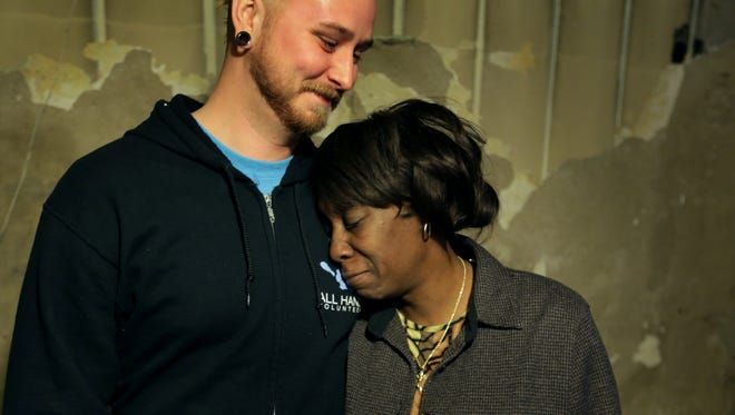 Jon Griswold, chief client services coordinator with All Hands Volunteers, shares a moment with Odessa Willis, 61, last month. He helped restore her flooded basement in Detroit.