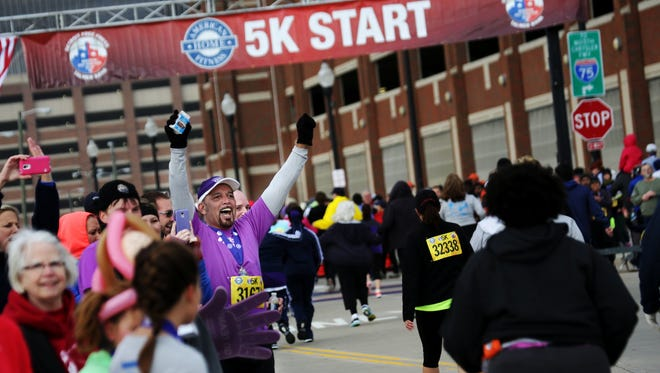 Josh Jaime, 58, of Berkley cheers on fellow runners near the finish line during the American Home Fitness 5K as a part of the Detroit Free Press/Talmer Bank Marathon along the Detroit Riverwalk in Detroit on Saturday, Oct. 18, 2014.