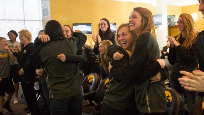 Iowa's Melissa Dixon hugs Ally Disterhoft as the Hawkeyes go into the 2015 NCAA women's basketball tournament as a No. 3 seed, starting in Iowa City, during a watch party at Carver-Hawkeye Arena on Monday, March 16, 2015. David Scrivner / Iowa City Press-Citizen