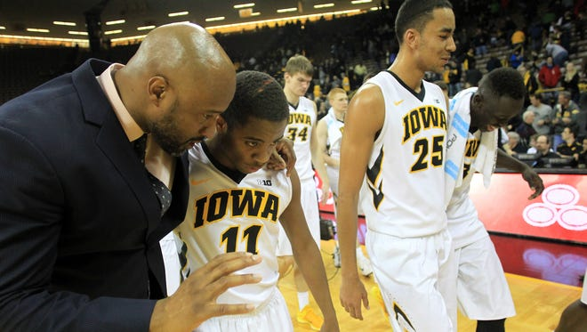 Iowa assistant coach Andrew Francis, left, talks with Trey Dickerson after Dickerson's final game as a Hawkeye on Feb. 19 against Rutgers.