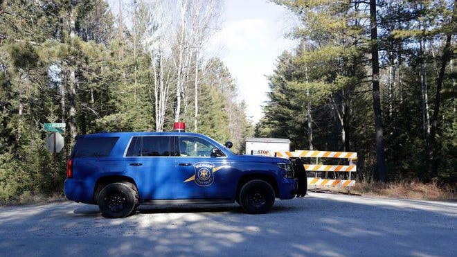 A Michigan State Trooper vehicle blocks a road near the area where a Wisconsin Air National Guard fighter jet crashed in the Upper Peninsula in the northeastern corner of Delta County, which hugs Lake Michigan, in a rural area within the Hiawatha National Forest.