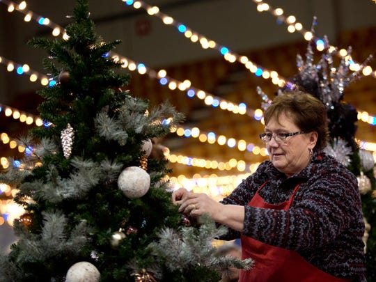 Deb Callahan, of St. Clair, decorates a tree in preparation for the Festival of Trees Wednesday, December 2, 2015 at McMorran Arena in Port Huron.