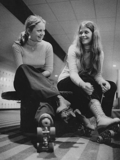 Cindy Preston (left) and Debbie O'Neal tie their skates at the United Skates of America in this 1974 photo.