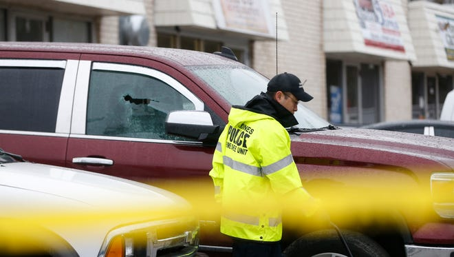A crime scene worker passes by a shattered windown of a car in the J & J Pizza parking lot Sunday, April 2, 2017, at the scene of an early morning shooting at 2500 Martin Luther King, Jr., Parkway in Des Moines.