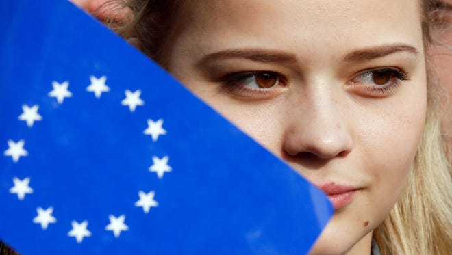 A young Ukrainian student holds a flag with the European Union emblem on April 5, 2016, ahead of a Dutch referendum.