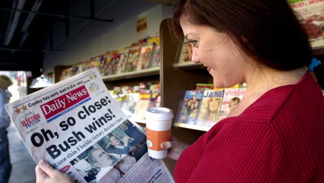FILE - In this Nob. 8, 2000 file photo, a woman reads a Los Angeles Daily News front page headline declaring Republican Texas Gov. George W. Bush the victor over Vice President Al Gore in the presidential election at a newsstand in the Hollywood section of Los Angeles. Newspapers across the country prematurely declared Bush the winner, even as Florida's crucial votes were still being counted. What happens if America wakes up on Nov. 9 to a disputed presidential election in which the outcome turns on the results of a razor-thin margin in one or two states, one candidate seeks a recount and the other goes to court? (AP Photo/Nick Ut, File)