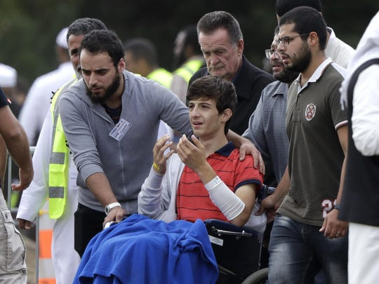 Zaed Mustafa, in wheelchair, brother of Hamza and son of Khalid Mustafa killed in the Friday, March 15 mosque shootings reacts during their burial at the Memorial Park Cemetery in Christchurch, New Zealand, Wednesday, March 20, 2019.