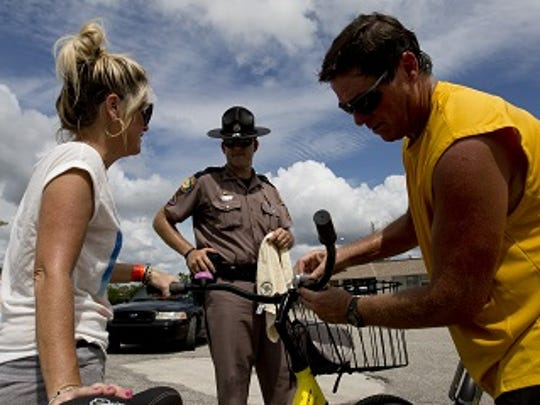 Dan Moser, right, an EMS injury prevention outreach worker for pedestrians and bikers attaches a light to Fort Myers Beach resident Shannon Korvanen's bike with the help of Florida Highway Patrol trooper, John Schultz, center, Fort Myers Beach in 2014.  The Florida Highway Patrol, along with the Lee County Sheriff's Office were taking part in the third quarterly wave of Operation P.E.D.S.