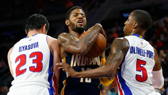 Indiana Pacers forward Paul George (13) drives between Detroit Pistons forward Ersan Ilyasova (23) and Kentavious Caldwell-Pope (5) in the first half of an NBA basketball game Saturday, Dec. 12, 2015, in Auburn Hills, Mich.