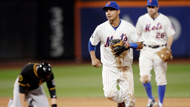 The Mets' Ruben Tejada, center, and teammate Daniel Murphy head to the dugout after Tejada forced out Pittsburgh's Neil Walker, left, to begin a double play in the eighth inning on Tuesday.