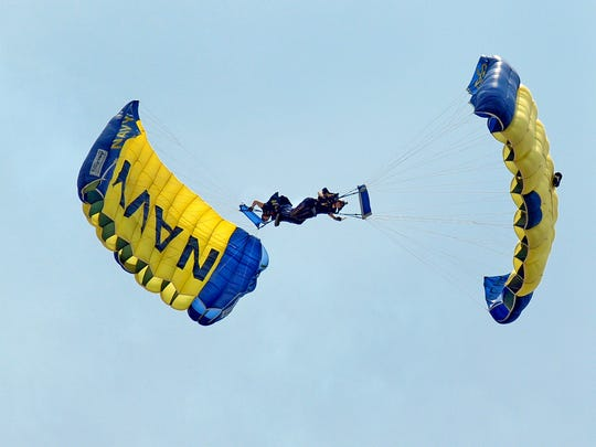Members of the United States Navy Seals Leap Frogs Justin Gaumy and Thomas Kinn parachute onto the beach during the National Anthem at the Ocean City Air Show 2011. The show includes teams showing off acrobatics and formations by civilian and military aircraft, a U.S. Navy Seals Flag Jump, a C5M Super Galaxy flyby and an A-10 Warthog demo. The Ocean City Air Show continues Sunday at noon, with show center at 16th Street oceanside.