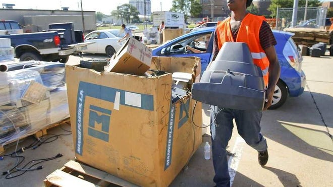 Derek Villarreal carries a TV set in October 2015 during the first electronic recycling event held by the city of Topeka and Shawnee County. This year's version of that event will not take place, the city announced Friday.