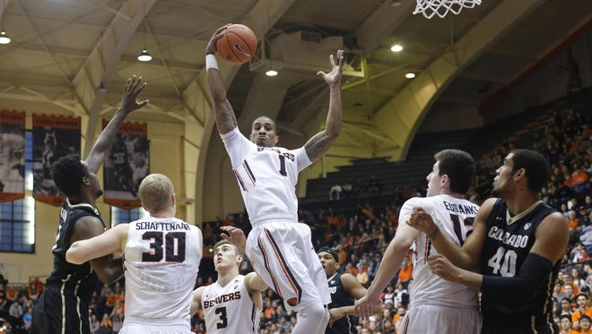 Oregon State's Gary Payton II, center, grabs a rebound in the first half of an NCAA college basketball game in Corvallis, Ore., on Saturday, Feb. 6, 2016.