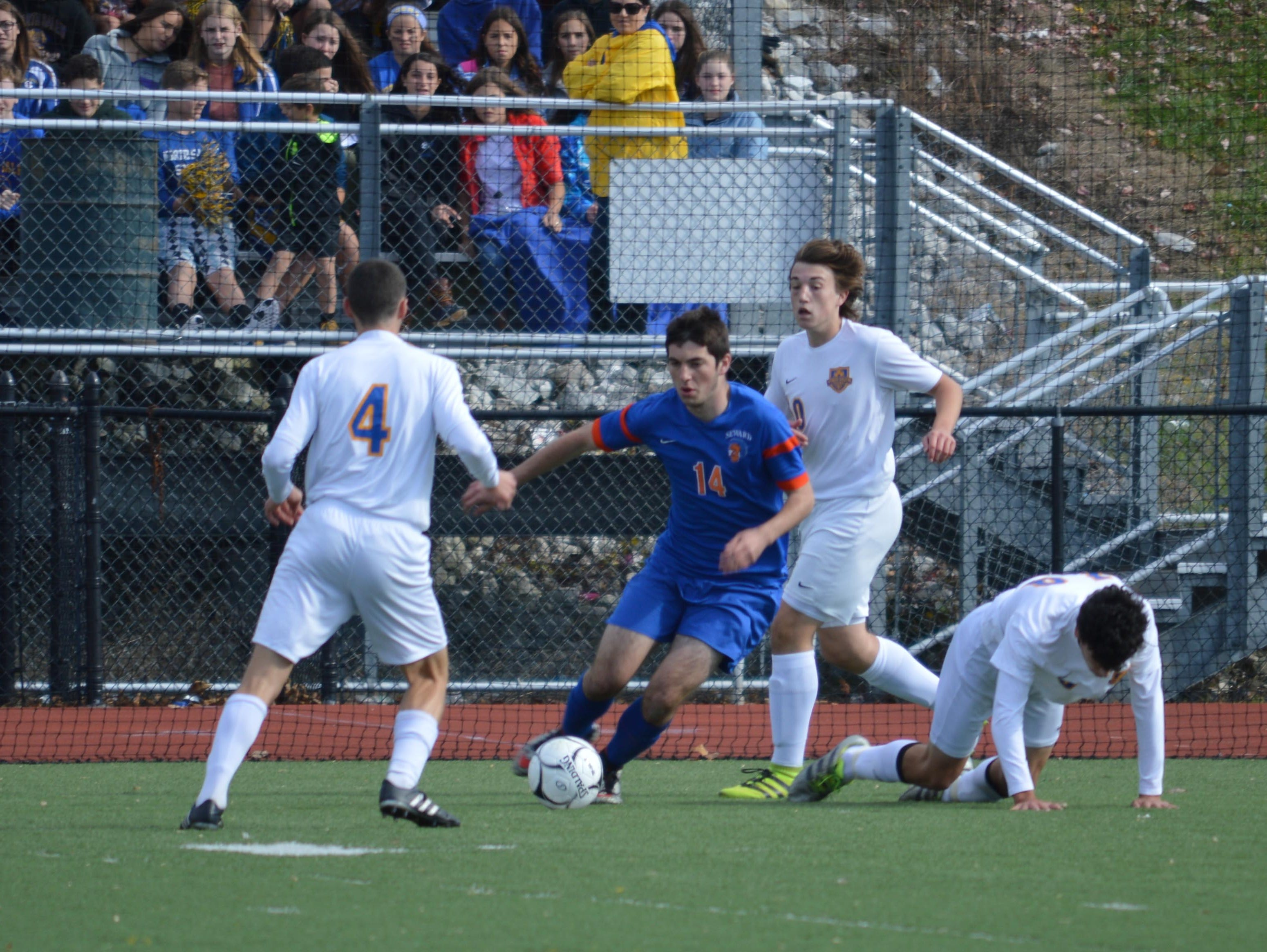 Seward's Jack Gardiner attempts to play the ball around North Salem's Michael Selzer (4), John Martabano (standing) and Mark Ribaudo (on knees) during the Class C Regional Game at Byram Hills High School on Nov. 5, 2016.