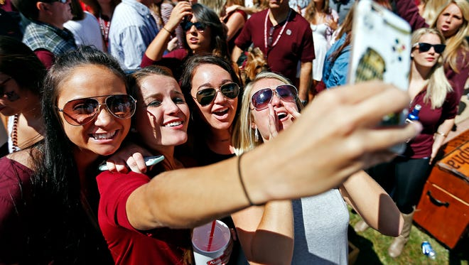 Carly McCarthy, Miranda Pierce, Olivia Post and Brittany Hisay, from left, sing a Bon Jovi song into their cellphone prior to the start of the Missouri State Bears' home opener game against the Chadron State Eagles at Plaster Stadium in Springfield, Mo. on Sept. 12, 2015.