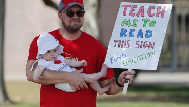 """Jon Kreibich holds his daughter, Fallon, during a #RedForEd """"Parents Stand for Teachers"""" rally at the Capitol in Phoenix on April 29, 2018."""