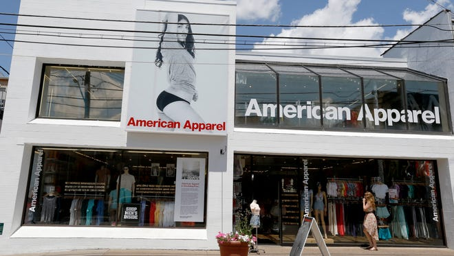 Passers-by walk down the street past the American Apparel store in the Shadyside neighborhood of Pittsburgh.