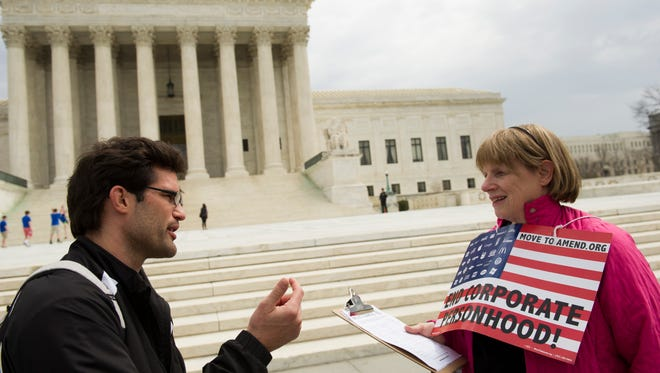 Joan Stallard, right, of Washington D.C., talks about the Supreme Court's McCutcheon v. FEC decision with Scott Dorn of Washington D.C., in front of the court April 2.