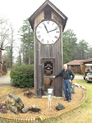 """Jimmy Hayes stands by the 20-foot tall """"great great grandfather clock"""" he built on his homestead in Pineville in 2003."""