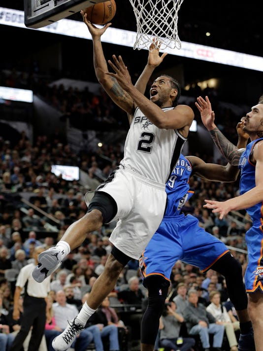 San Antonio Spurs' Kawhi Leonard (2) takes a shot after getting through Oklahoma City Thunder's Serge Ibaka, rear, and Steven Adams, right, during the second half in Game 2 of a second-round NBA basketball playoff series, Monday, May 2, 2016, in San Antonio. (AP Photo/Eric Gay)