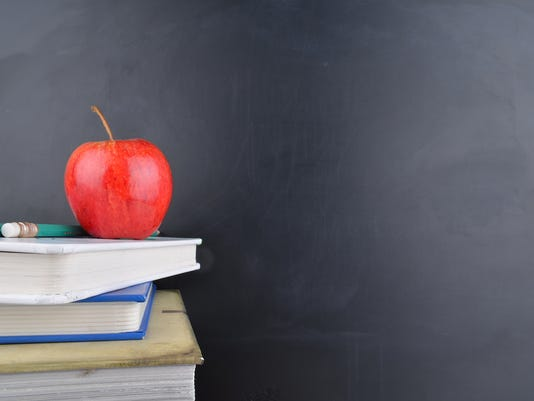 Classroom concept with books an apple and blackboard with handwriting