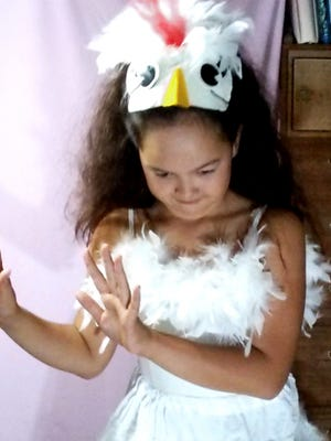 Amelie practicing a dance routine at home in her chicken costume.