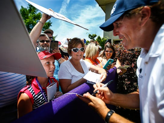 Phil Mickelson (right) signs autographs for fans at
