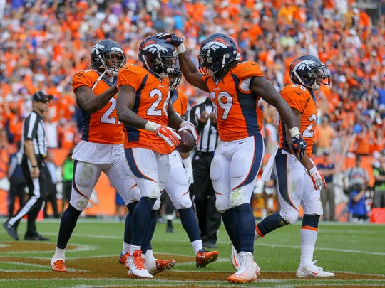 Broncos defensive back Darian Stewart (26) celebrates with Danny Trevathan (59) and Aqib Talib (21) after making a game-ending interception in the fourth quarter against the Ravens.