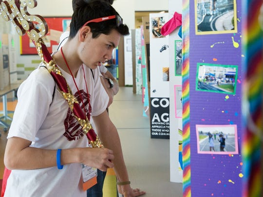 Adan Armijo, 18, of Valley High School in Albuquerque, looks over a poster board from the Centennial High Schools Student Council showing a project they worked on during the Student Council Conference on Friday, Feb. 10, 2017, at Centennial High School.
