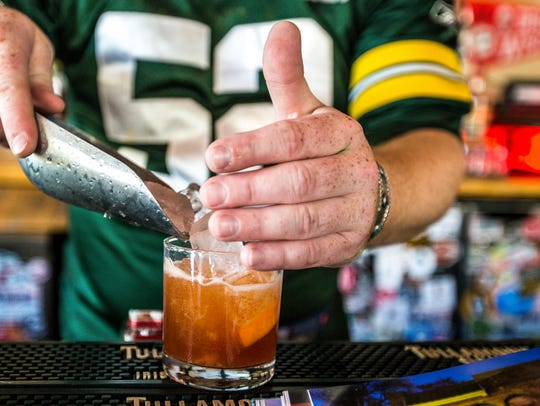 A bartender prepares an Old School Old Fashioned at