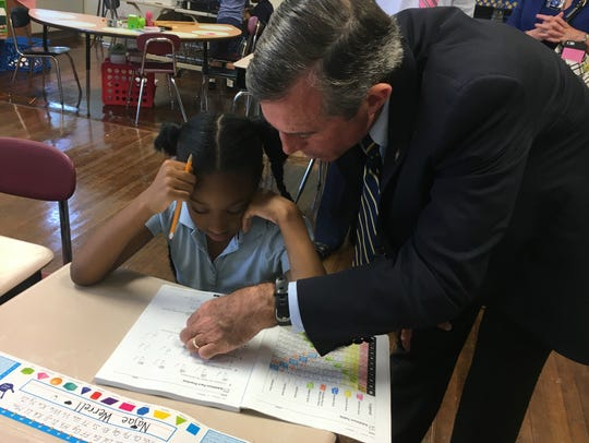 Gov. John Carney helps a student at Bancroft Elementary