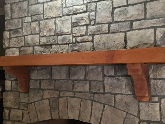 BEFORE: The warm tone of the pine mantel clashed with the cool gray tones of the stone.