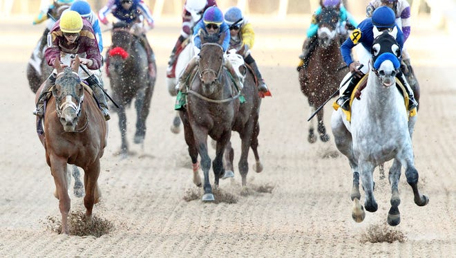 Cupid, right, fended off Whitmore, outside, to win Saturday's Rebel Stakes at Oaklawn Park.
