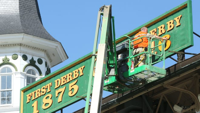 A worker updates Churchill Downs' grandstand signage Friday morning.