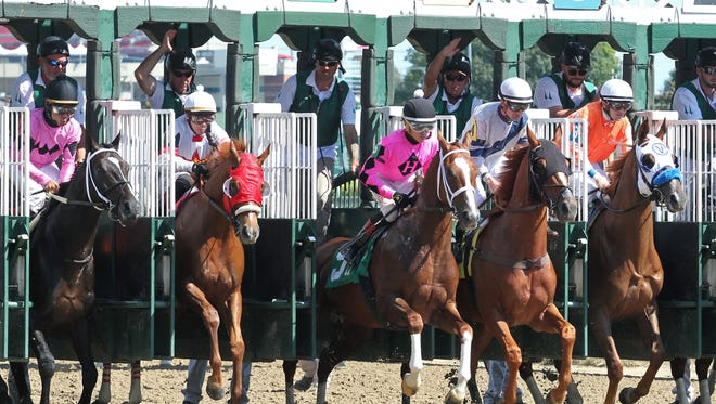 Horses break from the gate at Churchill Downs