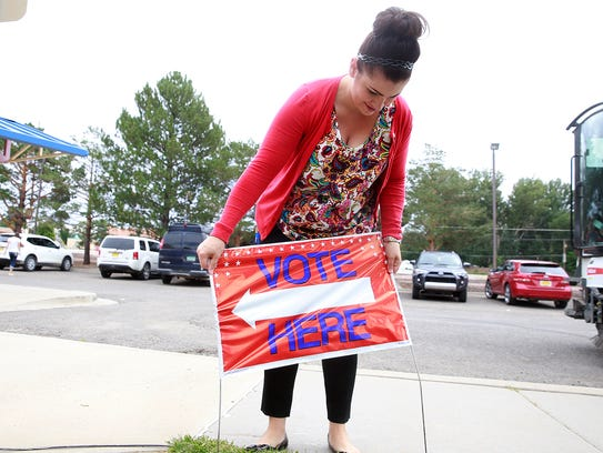 City Clerk Erikka Martinez places a sign to let residents know where to vote on Aug. 16, 2016, at the Bloomfield Municipal Complex in Bloomfield. Martinez has resigned as city clerk.