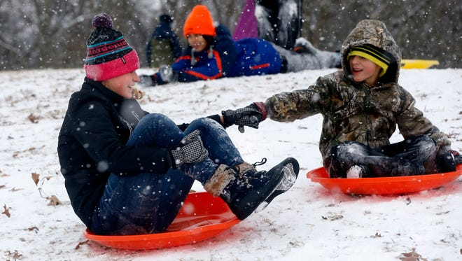 Sarah Sneed, 16 and Zachary Sneed, 7, hold hands as they slide down a hill while sledding at Barfield Park, on Tuesday, Jan. 16, 2018.