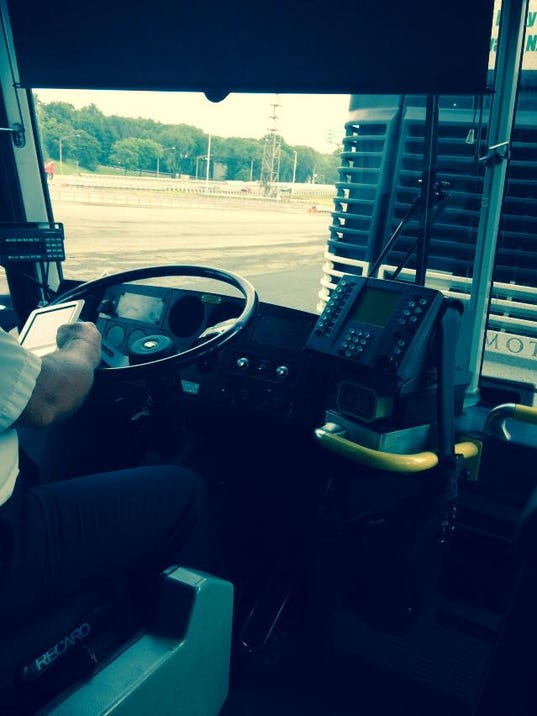 NJ T driver at wheel with e-reader.jpg