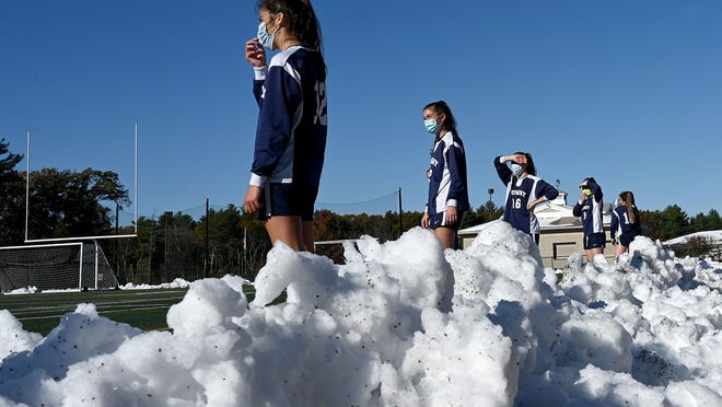 The Medway bench follows the action from in front of a snowbank during a game against Holliston at Medway High School on Saturday. The team assisted in clearing the field after Friday's snowstorm.
