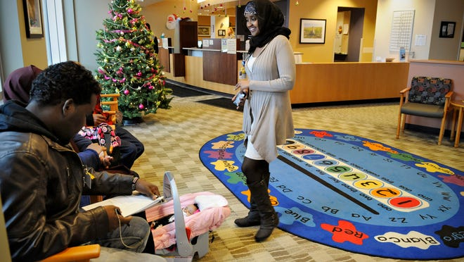 Amina Ahmed, community health worker at the CentraCare Health Plaza, talks with a Somali family and their interpreter to make sure they have everything they need before an appointment Dec. 19.