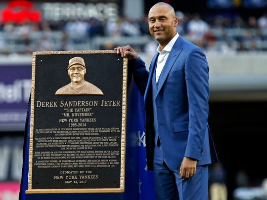 Former New York Yankees shortstop Derek Jeter poses for a photo with his Monument Park plaque during a pre-game ceremony Sunday, when his jersey number also was retired.
