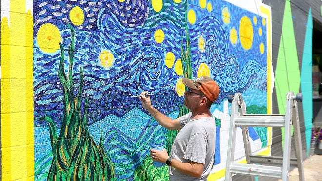 "Dover artist Jon Stucky works on an adaptation of Vincent van Gogh's ""Starry Night"" on the south side of Alley Cats Marketplace in downtown New Philadelphia."