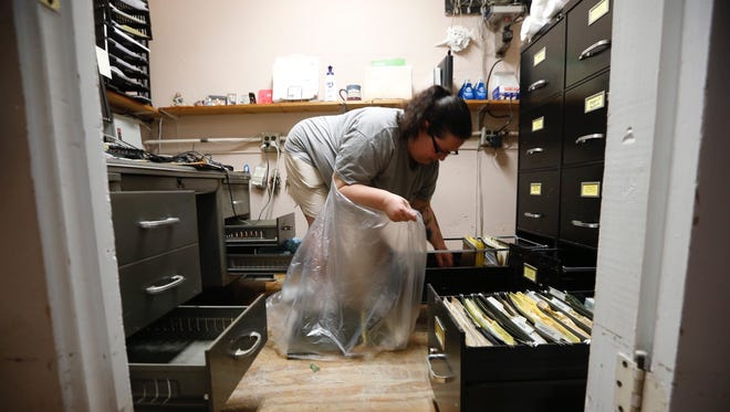 Jodi Slone cleans out files that were ruined at her family business, House Calls, in Norwood Monday. The cleaning company lost several vacuum cleanings and other equipment.