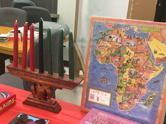 Books, games and puzzles for kids sit alongside the seven candles in a candelabra that represent the seven principles of Kwanzaa. A group celebrated the event Dec. 10, 2016 at the Whitney Senior Center.